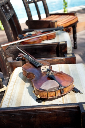 Violin and fiddle stick on chair, closeup