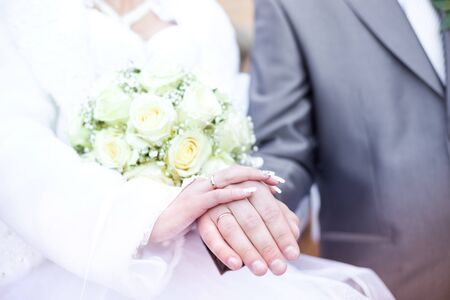Hands and rings on wedding bouquet, closeup photo