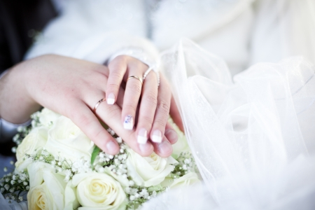 Hands and rings on wedding bouquet, closeup