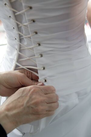 helping with brides corset, wedding white dress photo