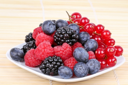 Assortment of sweet berries on white plate, closeup