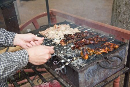 Process of cooking meat on barbecue, turning skewer photo