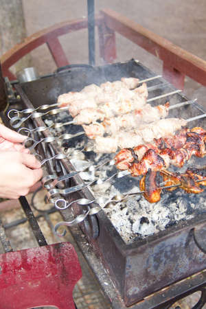 Process of cooking meat on barbecue, hand turning skewer photo