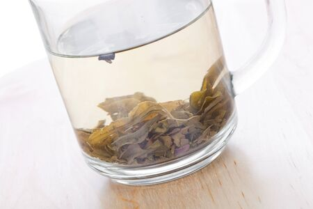 non alcoholic: Green tea in glass cup with leafs, closeup on wooden table