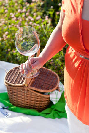 Woman holding empty wineglass, outdoor photo