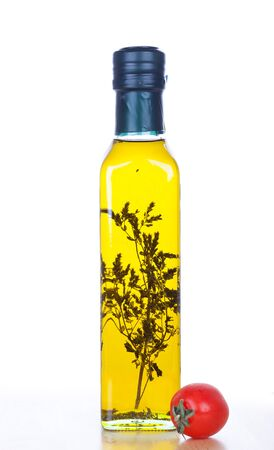 Olive oil in glass bottle with rosemary inside and cherry tomato, closeup on white photo
