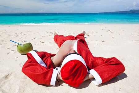 Santa Claus on beach relaxing, enjoing summer photo