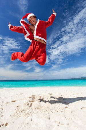 Santa Claus is jumping on beautiful beach photo