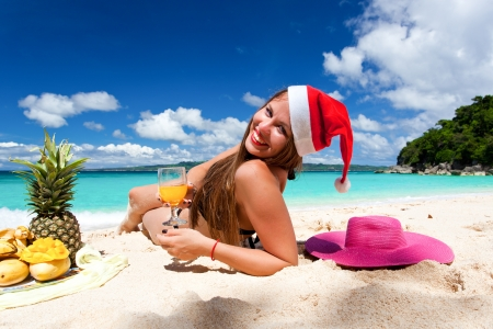 Young woman celebrating Christmas, having exotic picnic with fruits photo