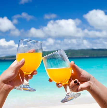 Cocktails on beach in female hands, cheers Stock Photo