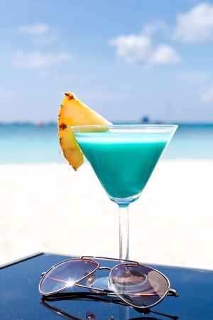 Blue Curacao cocktail with slice of ananas on white beach Stock Photo