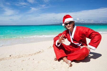 Santa man on beach near ocean photo