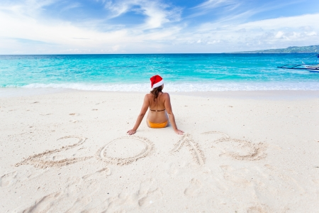 Happy woman on the beach with Santa Claus hat, 2013 Stock Photo