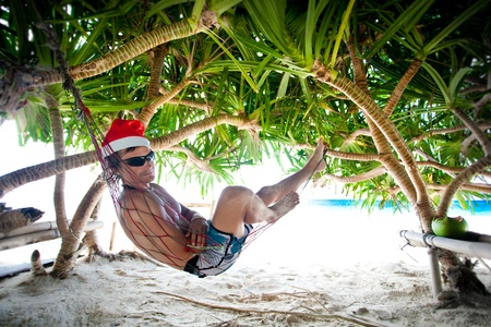 dominican: Man in Santa hat in hammock on tropical beach Stock Photo