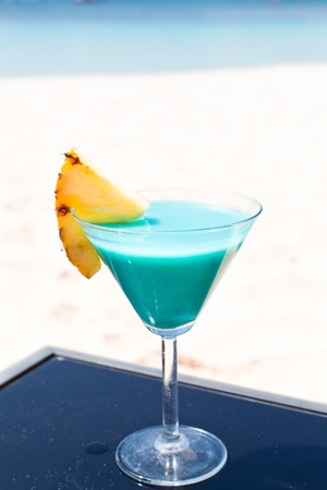 Blue Curacao cocktail with slice of ananas on white beach photo