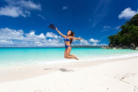 Beautiful woman jumping on beach with a hat photo