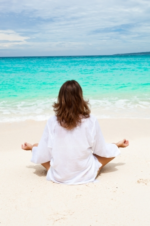 Woman meditating on beach in lotus position photo