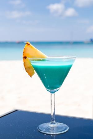 Blue Curacao-Cocktail mit Scheibe Ananas auf weißem Strand