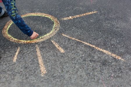 chalks: Child drawing sun on asphalt  by chalks