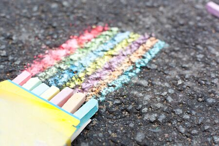 Set of colorful chalk lying on asphalt  photo
