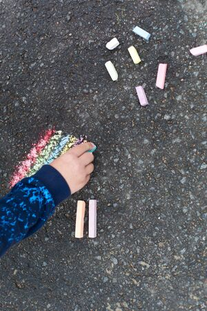 Child hand with colorful chalk on asphalt photo