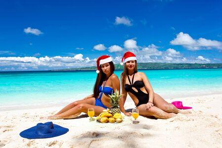 Two Woman celebrating Christmas on tropical beach photo