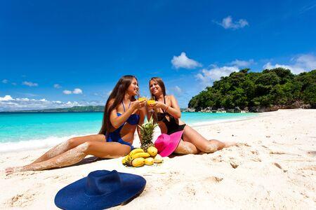 Two girls having picnic on tropical beach photo
