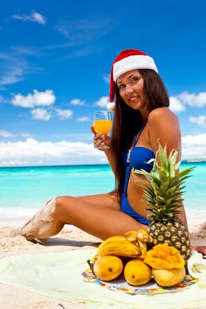 Two funny girls in santa hat on beach, celebrating Christmas photo