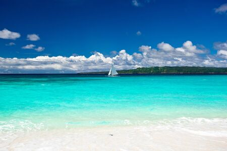 Beach with sailboat in ocean, Philippines photo