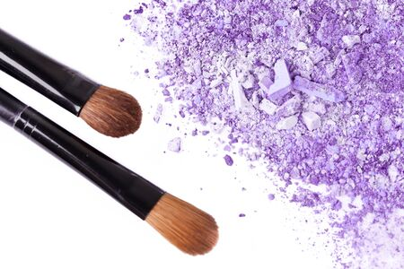 Crumbled eyeshadow with brush, closeup on white photo