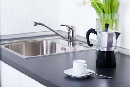 coffeemaker: Coffeemaker and cup of coffee in kitchen interior