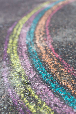 chalk drawing of rainbow and color chalks on asphalt photo