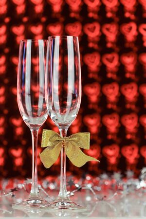 Two glasses with champagne on red heart background photo