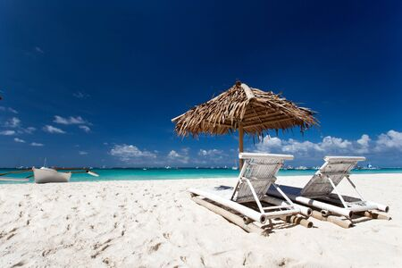 Sun umbrella with chair longues on tropical beach, Philippines, Boracay photo