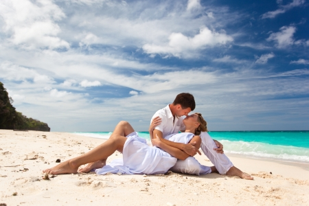Loving pair sitting on the beach photo