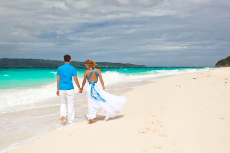 Loving wedding couple on beach in white dresses