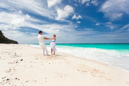 pareja bailando: Amar a bailar boda pareja en la playa en vestidos blancos Foto de archivo
