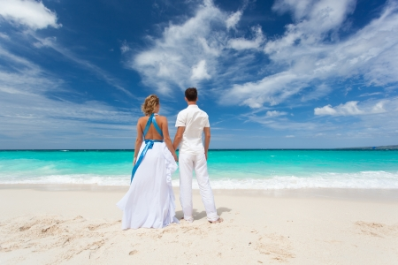guy on beach: Loving wedding couple on beach in white dresses