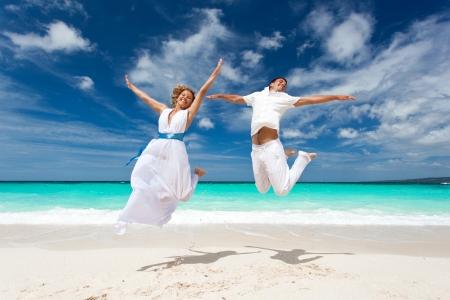 boda en la playa: Boda pareja feliz saltando en la playa