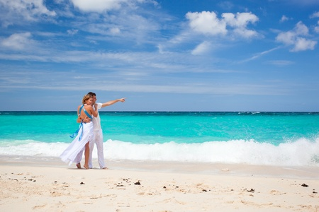 Bride and groom on tropical beach, walking photo