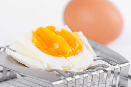 Cutted egg on cutter, closeup on white