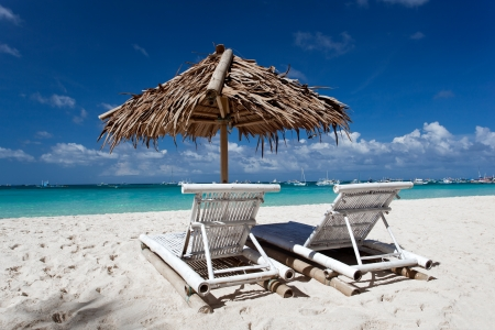 Sun umbrella with chair longues on tropical beach photo