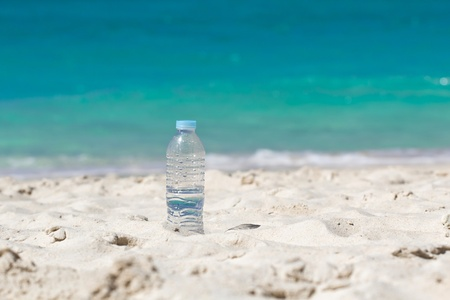Drinking water in bottle on sand on beach photo