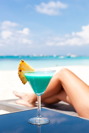 Resort Vacation. Woman relaxing with Blue Curacao Cocktail. (Focus is on glass)  photo