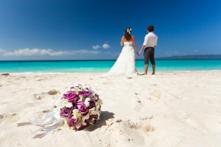 boda en la playa: Ramo de la boda en el fondo de la boda pareja, besar en la playa
