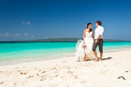 Wedding couple walking at the beach photo