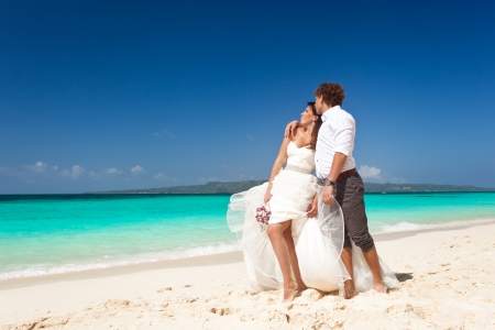 woman beach dress: Bride and groom on the beach. Tropical wedding