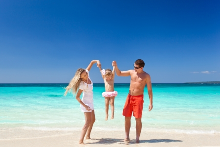 Parents throwing their daughter in air at the tropical beach photo