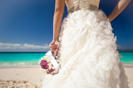 Wedding bouquet in brides hand on beach photo
