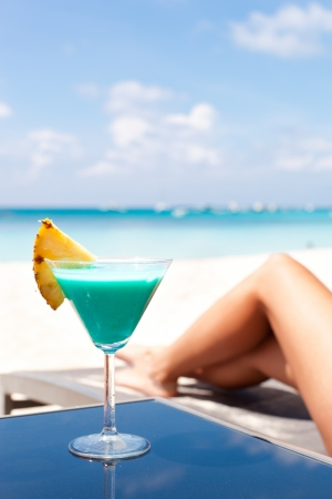 the chaise lounge: Resort Vacation. Woman relaxing with Blue Curacao Cocktail. (Focus is on glass)